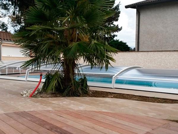 Abri de piscine téléscopique modèle Chypre installé à Meximieux (01) avec guide au sol sur 1 coté