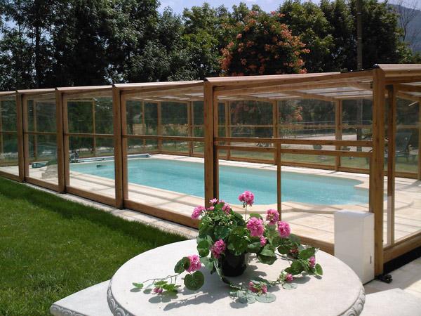 Abri de piscine Capri Haut installé à Voreppe près de Grenoble (38), motorisé avec 1 guide au sol d'un seul coté. Couleur bois et façade basculante.