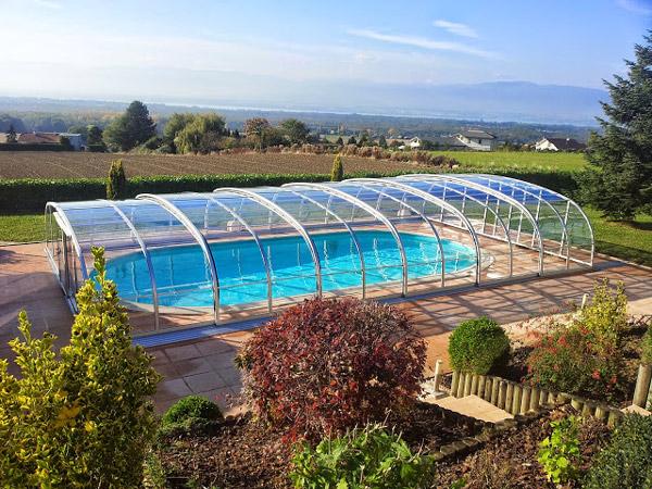 Abri de piscine modèle Baléares Thermo installé à Anemasse (74) près du lac Léman, entièrement transparent avec guide au sol.